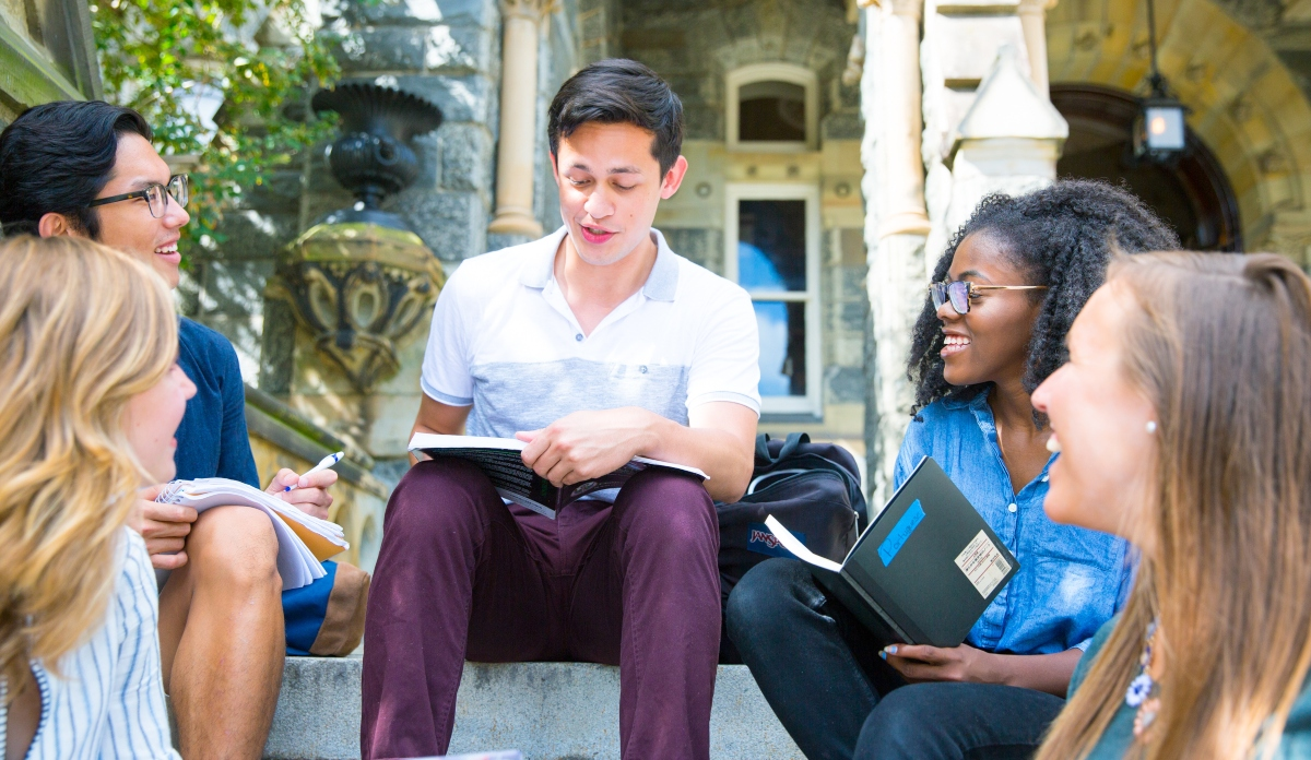 Five students studying together on the steps of Healy Hall